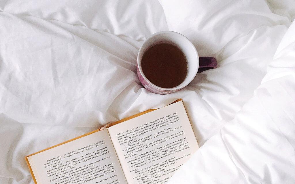 Coberta, xícara de café e livro